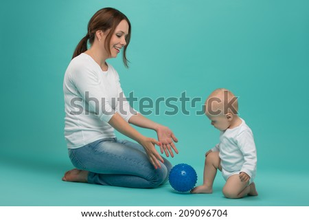 Young Caucasian attractive smiling mother playing with her cute little son with a ball, baby boy wearing bodysuit isolated on blue - stock photo