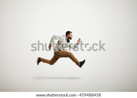Young Caucasian bearded man in casual clothes is running violently isolated over white background