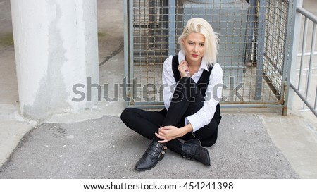 Young Caucasian blonde girl in black and white outfit is sitting and posing in front of the metal cage in the concrete surroundings. - stock photo