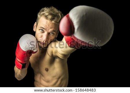 Young caucasian boxer with gloves performing a punch.