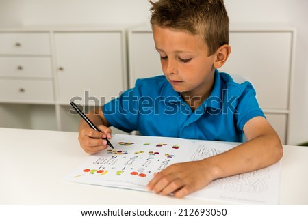 Young caucasian boy doing his elementary school homework while sitting at desk. - stock photo