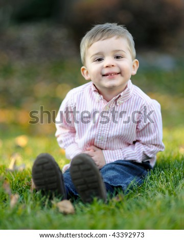 Young caucasian boy in autumn grass - stock photo