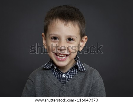 Young caucasian boy laughing on a black background