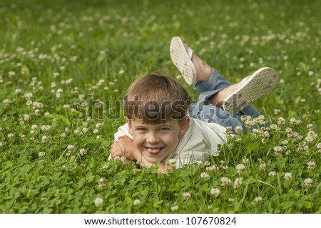 Young Caucasian Boy lying in the grass on his stomach with his hands on his face, a cute look on his face, and ankles crossed. Four to  Five years old - stock photo