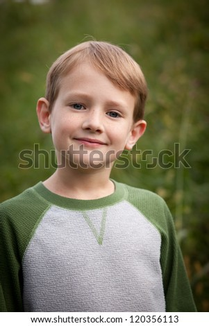 Young Caucasian boy smiling with a blurred green background
