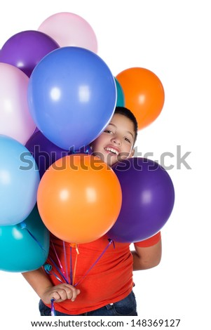 Young caucasian boy wearing an orange t-shirt and blue jeans. The boy is holding a bunch of bright coloured helium balloons.