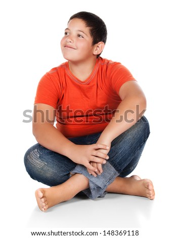 Young caucasian boy wearing an orange t-shirt and blue jeans. The boy is sitting and smiling. - stock photo