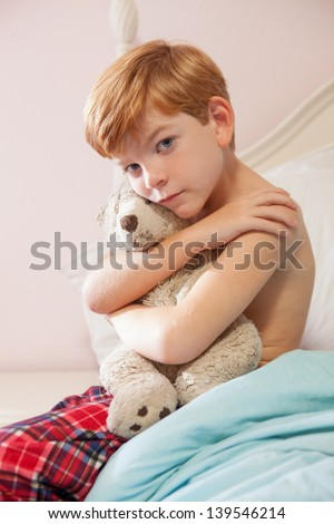 Young caucasian boy with red hair, sitting on edge of bed in pajama bottoms, with sad expression, holding teddy bear. - stock photo