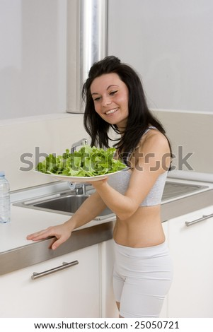young caucasian brunette in gym wear,showing a salad dish smiling in her kitchen.Concept of healthy lifestyle with a correct diet.