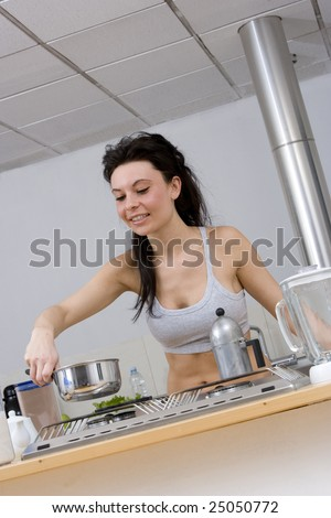 young caucasian brunette in kitchen in front of stowe while preparing breakfast in gym wear.