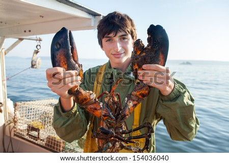 young, caucasian, brunette man holding large, weathered lobster, Maine, USA - stock photo