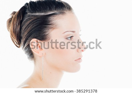 Young caucasian brunette poses for a beauty session in studio with white background