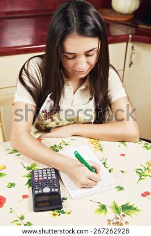 Young caucasian brunette woman making calculations at the kitchen table high angle view - stock photo