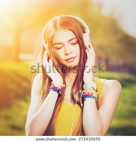 Young Caucasian brunette woman with headphones outdoors on sunny summer day. Millennial teenage girl listening to music wearing yellow shirt and vibrant jewelry. Square format, retouched, filter. - stock photo