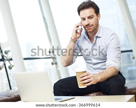 young caucasian business people making a call using mobile phone in modern office. - stock photo