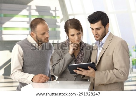 Young caucasian business people with tablet computer at office lobby. Standing, looking at screen, wearing suit.