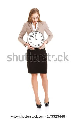 Young caucasian business woman holding clock. Isolated on white.