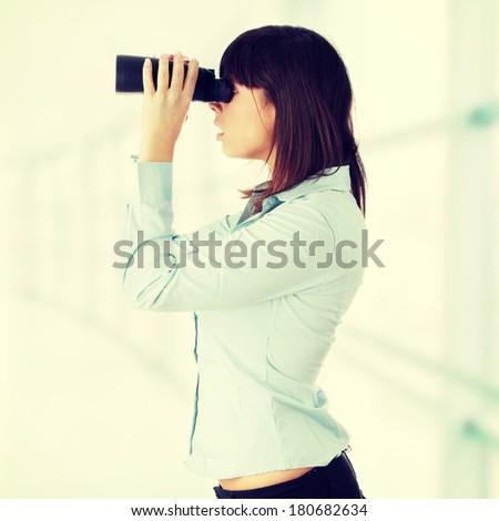 Young caucasian business woman looking through binocular  - stock photo