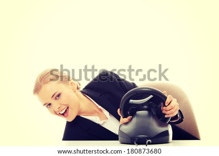 Young caucasian business woman playing on computer (with steering wheel)