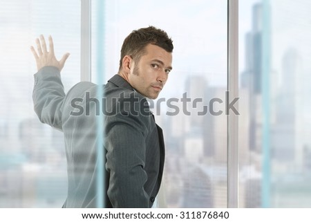 Young caucasian businessman in front of window looking back at business office. Hand on glass, wearing suit, serious. Focus in background, looking at camera. - stock photo