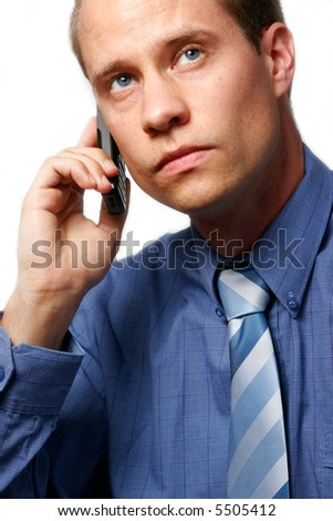 Young Caucasian businessman listening to his mobile phone, against a white background. - stock photo