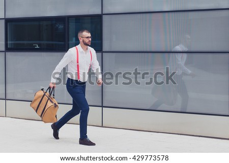 Young caucasian businessman running in the city with a bag. Copy space