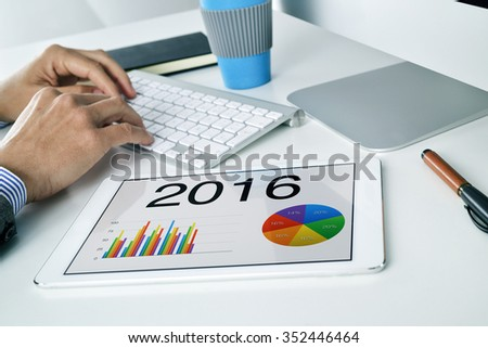 young caucasian businessman sitting at his office desk, with a tablet computer with different charts with the economic forecast for 2016 in the foreground - stock photo