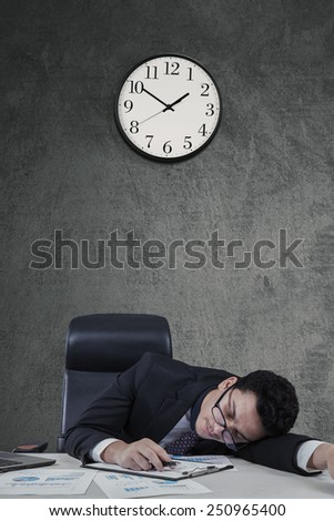 Young caucasian businessman sleeping on desk with clock on the wall - stock photo
