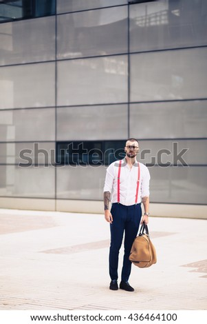 Young caucasian businessman standing outside of a modern architecture office building in the city looking at camera. Copy space - stock photo