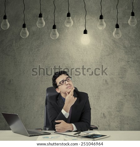 Young caucasian businessman while thinking and looking at bright lightbulb - stock photo