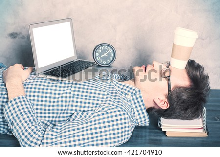 Young caucasian businessman with blank white laptop screen sleeping on desktop with coffee cup on forehead. Mock up - stock photo