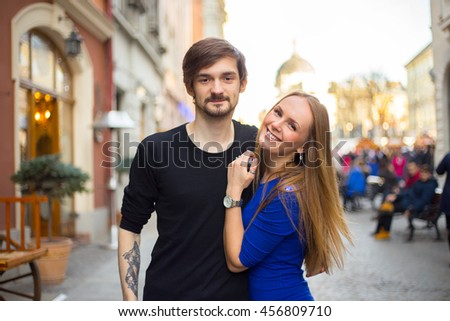 Young caucasian cheerful couple at the european city with selective focus on their faces - stock photo