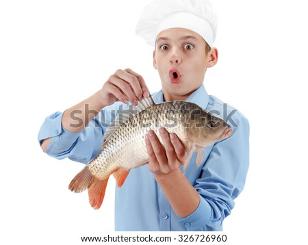 Young caucasian chef holding a fish carp. Hilarious cooking wholesome food. Isolated on white background
