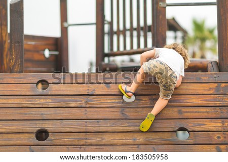 Young caucasian child playing on the playground, climbing on the wooden wall - stock photo