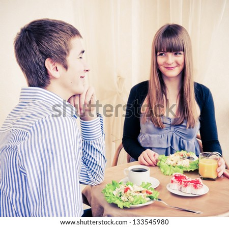 Young caucasian couple dining in restaurant and smiling. - stock photo
