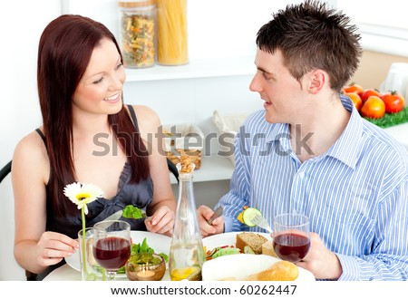 Young caucasian couple having dinner at home in the kitchen - stock photo
