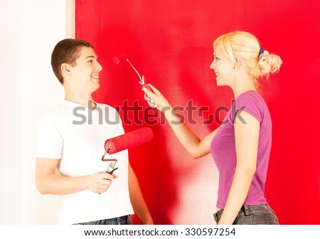 Young caucasian couple having fun painting wall in a new home - stock photo