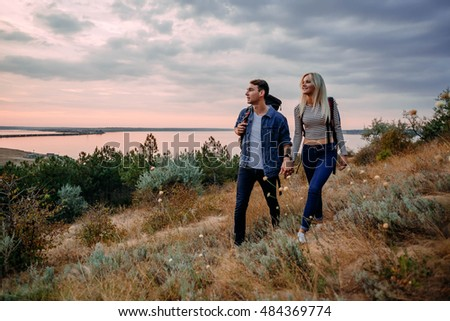 Young caucasian couple hiking outdoors with backpacks during sunset