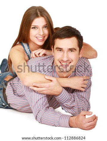 Young caucasian couple lying on floor and hugging , isolated on white background - stock photo