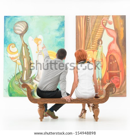 young caucasian couple sitting on a wooden bench in an art gallery pointing at some painting - stock photo