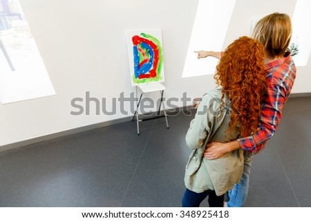Young caucasian couple standing in a gallery and contemplating abstract artwork - stock photo