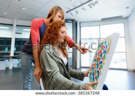 Young caucasian couple standing in a gallery and contemplating artwork - stock photo