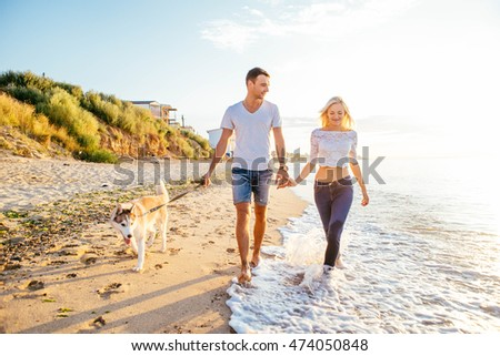 young caucasian couple walking on beach with siberian husky dogs