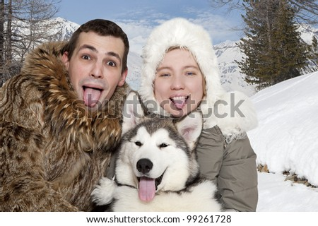 Young caucasian couple with a malamute puppy show their tongues - stock photo