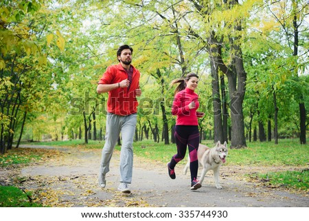 young caucasian couple with husky dog running in autumn park, couple jogging together - stock photo