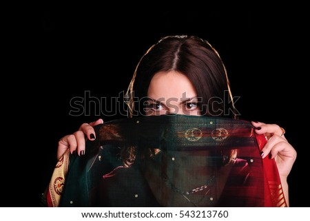 Young caucasian dark-haired pretty woman hides a face behind a piece of Indian sari. (Studio low key shot)