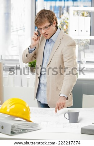Young caucasian engineer talking on mobile phone and pointing at plan at office. Folder and hardhat on table. - stock photo