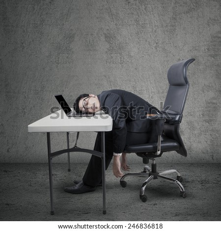Young caucasian entrepreneur in business suit, sleeping on laptop computer at table - stock photo