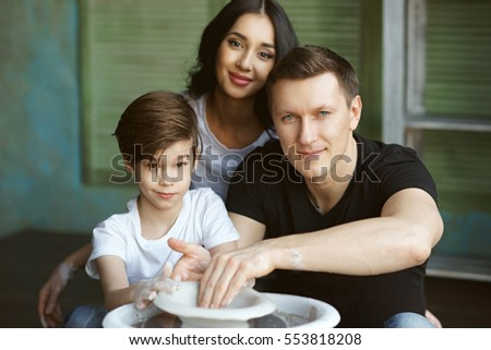 Young caucasian family working on potter's wheel. Handsome father, beautiful mother and young son. Pottery classes. Dirty Hands. Parents enjoying time together with their child.