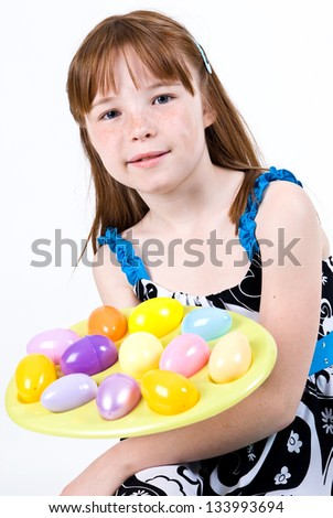 Young Caucasian female child holding a plate of Easter eggs